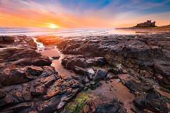 Bamburgh Sunrise (MatthewSavage.Photography) Tags: bamburghcastle northumberland england uk coast coastline coastal sea water waves sun sunrise colour orange rocks castle bamburgh ngc