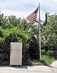 The Glory Of Old Appliances (Eyellgeteven) Tags: flag usa appliance appliances refridgerator fridge abandoned used wtf weird unusual bizarre oldglory americanflag american patriotic discarded refuse retired funny usflag flagpole sidewalk kitchen eyellgeteven