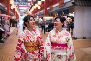 Happy mother and daughter in kimono walking together in shopping mall