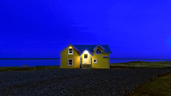 When the night falls (PokemonaDeChroma) Tags: house hotel flat beach blue hour yellow sky horizon water gravel halicountry iceland atlantic sea iphoneography iphonese 169 door window roomwithaview hofn
