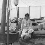 Inuit woman sitting inside a tent that has a stove, Kangiqsujuaq, Quebec / Inuite assise dans une tente munie d'un poêle, Kangiqsujuaq (Québec)e008446973-v6 thumbnail
