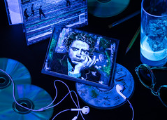Music CD's (Verónica Mayer (-Urrutia)) Tags: music audio cd futurist downey robert uv light blacklight still life studio headphone moscot sunglasses pencil face cover sound desk drink tonic quinine fluorescent blue ice cube