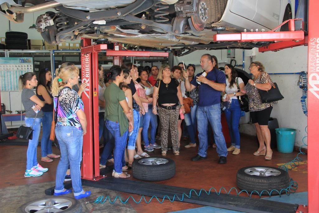 Turma de Mecânica com salto alto em uma aula prática.