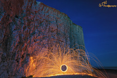 Cliff Sparks (Gavmonster) Tags: nikon nikond7000 d7000 gswphotography landscape sky land sussex uk unitedkingdom lightpainting longexposure blue gold 30seconds eastsussex night evening wirewool circle spinning steelwool sparks cliff sevensisters beach pebbles chalk rocks sea orange fire englishchannel southdowns
