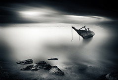 The Old Boat that Did not Sail the Lonely Planet (Gianmario Masala) Tags: textures textured photoshop gimp blur blurry rocks reefs photograph gianmariomasala sea boat contemplative blackandwhite monochrome toned mono sky water calm smooth longexposure canon550d minimal