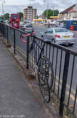 Locked Up (M C Smith) Tags: cycle locked railings traffic bus shops blue sky clouds lamps white pentax k3 flats red