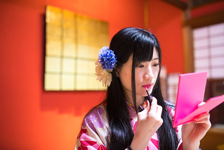 Young woman in Kimono making-up in Japanese tatami room