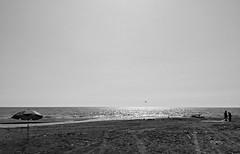 fishermen... ((rino)) Tags: bw beach flickr rino fishermen water sea birds umbrella sand