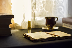 Open book on a table with a candle, day light (Sandronn) Tags: book burning candle candlestick education history holder library light literature material old oldfashioned open page paper reading religion studying table text wisdom