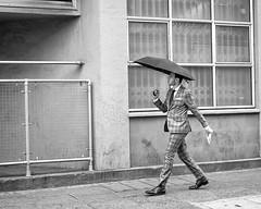 Singin' and Dancin' in the Rain. (James- Burke) Tags: 27mm bricklane candid fuji fujixt1 london street streetblackandwhite streetphotography uk monochrome people umbrellas rain rainyday walking dancing graphic lines bw man manwalking