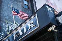 Fair? (tommiaarnio) Tags: new york city street north america usa us shop sign billboard security camera girl scared woman flag stars stripes brick wall summer cold scary urban explore discover concrete tommi aarnio tommy aarnyo fine art candid landscape orientation d800 nikon nikkor 2470mm