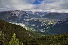 An Amazing View of the Bow Valley (Banff National Park) (thor_mark ) Tags: nikond800e lookingne day2 triptoalbertaandbritishcolumbia banffnationalpark capturenx2edited colorefexpro tunnelmountain mountrundle cascademountain bowriver river rockymountains canadianrockies centralfrontranges vermilionrange banff stoneysquawmountain sawbackslateranges sawbackrange southerncontinentalranges southbanffranges rundlepeaks sulphurmountain mountgirouard eastbanffranges fairholmerange lakeminnewanka lake blueskieswithclouds trees evergreen outside nature landscape rollinghillsides mountains mountainsindistance mountainsoffindistance hillsides hillsideoftrees evergreens bowvalley sansonpeak citystreets street canvas portfolio project365 atopsulphurmountain alberta canada