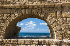 Ancient stone arch (Ivanov Andrey) Tags: aqueduct christianity series crusader archaeology history ruins wall sun arch shadow light fence sea noon wave wind sky cloud plant space outdoor color straightline shore stone block brick museum architecturalelement antique corner vertical horizontal perspective themediterraneansea caesarea thesea israel