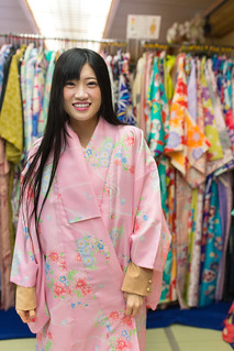 Young woman trying on Kimono at rental Kimono shop