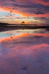 Beautiful sunset sky and Reflection in shallow sea water. (baddoguy) Tags: beach beautyinnature blue bridgebuiltstructure cloudsky coloredbackground copyspace dramaticsky horizon illuminated landscape locallandmark lowtide moored multicoloredbackground nationallandmark nopeople orangecolor pavilion photography pier reflection romanticsky roof saltwaterflats scenics seascape sheltering sunset thailand tourism tratprovince travel twilight vacations vertical wallpaper water webbanner woodmaterial