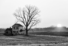 The Sun Sets on an Old Abandoned Farmhouse (SteveFrazierPhotography.com) Tags: bw monochrome blackandwhite farm house abandoned old spring sprintime stormy rainy clouds overcast illinois il farming farmland agriculture field plowed rural country countryside scene scenery landscape outdoor evening stevefrazierphotography chili art artwork vintage historic historical yesteryear hancockcounty township