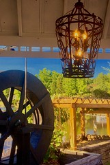 Frank's at the Old Mill, Fayetteville, GA (WorldExplorations) Tags: chandelier sunnyday summer sunshine vine gazebo pergola sky bluesky metal rustic light outdoorlight lamp iron millwheel wheel woodwheel wood engine waterengine waterpower industrial river pond water creek landscape lake whitewatercreek lakebennett south georgia fayettevillega fayetteville oldmill franksatoldmill