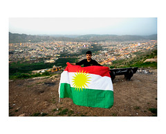 A man holds the flag of Iraqi Kurdistan. A spectacular view of Dohuk in the evening on the background. (Roman Lunin) Tags: iraq kurds kurdish flag dohuk kurdistan landscape view cityview middleeast documentary reportage people