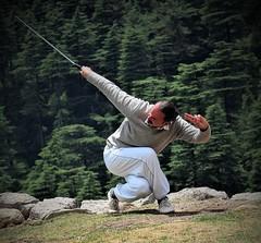 Tai chi master with sword (bearlike1) Tags: tai chi yoga dharamkot dharamshala sword trees mountain mountains cliff edge white grey green martial arts art dance style pose india indian french mcleod ganj himanchal pradesh