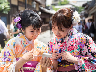 Two young women in kimono using smart phone in Kiyomizuzaka street, Kyoto