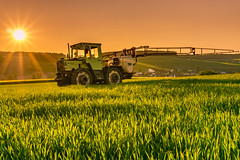 Tractor In The Sun (davidve1) Tags: tractor sun star yellow green spring field