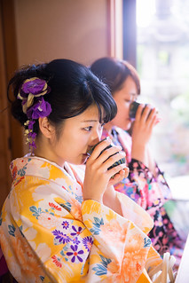 Two young women in kimono drinking Japanese tea in restaurant