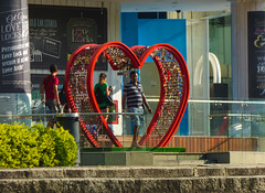 Love Struck (Steve Taylor (Photography)) Tags: art design sculpture red blue green asia singapore clarkequay central locksoflove padlock heart people man