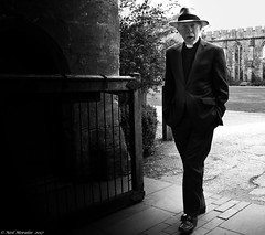 Some things don't change with the times. (Neil. Moralee) Tags: neilmoralee neilmoraleenikond7200 vicar priest clergy church religion uk gb bath wells somerset lay reader decon bishop palace nikon neil moralee black white bw bandw blackandwhite mono monochrome hat man old mature fashion panama shade shadow walking portrait candid gate gateway ruin building cathedral parish pastoral pastor dark enter stone