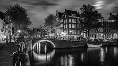 A shot in the dark (McQuaide Photography) Tags: amsterdam noordholland northholland netherlands nederland holland dutch europe sony a7rii ilce7rm2 alpha mirrorless 1635mm sonyzeiss zeiss variotessar fullframe mcquaidephotography lightroom adobe photoshop tripod manfrotto light licht night nacht nightphotography water reflection stad city urban waterside lowlight architecture outdoor outside waterfront gracht capitalcity capital illuminated building bridge canal keizersgracht boat traditional authentic classic blackandwhite blackwhite bw mono monochrome canalhouse grachtenpand longexposure 169 widescreen wideangle groothoek brug