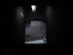 passing innocence (cherryspicks (on/off)) Tags: child monochrome street blackandwhite arch light dark city people introspective