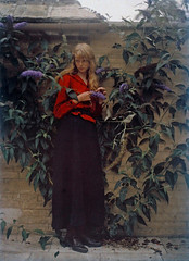 At the Garden Wall (kevin63) Tags: lightner old vintage antique retro woman photo color autochrome process 1900s garden wall vines house red blouse black skirt victorian edwardian picture long blonde hair romantic purple flowers lupins brick tile