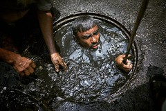 A sewer cleaner of Dhaka City Corporation cleaning out the city's sewers in Dhaka, Bangladesh.  Despite a rise in the number of deaths of manhole workers every year, workers regularly go into the manholes without any protective gear.  #sewer #cleaner #ban (auniket prantor) Tags: ludwig adult asia bangladesh cleaner cleaning danger dhaka dirty editorial hole horizontal human interest india lifestyles manhole men occupation photography poverty risk safety sewer smelling toughness water whole working work worker