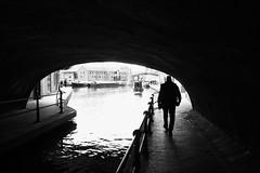 Along the canal (halifaxlight) Tags: england birmingham birminghamcanalnavigations worcesterandbirminghamcanal narrowboats bridge arch figure walking canal bw railing