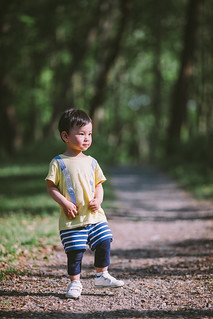 Front view of baby boy walking on footpath in forest