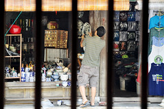 Trapped in a life of routine (Roving I) Tags: shopkeepers lifestyle workers shops stores tourism chinaware preparing opening retail teapots plates bars hoian vietnam