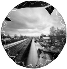 Merged Wagons (batuda) Tags: pinhole obscura stenope lochkamera analog analogue lid beer beerlid 25 film paper ortho orthochromatic photocopy d76 bw blackandwhite monochrome wide wideangle perspective town city rail railway train wagons sky clouds road station house tree trees radviliškis lietuva lithuania wppd movement motion