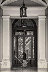 'Knockin' On Heaven's Door' (Canadapt) Tags: woman janitor bucket mop pillar entrance building window reflection door lamp bw sepia seville spain canadapt