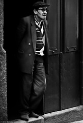 Dark Doorways. (Neil. Moralee) Tags: neilmoralee neilmoraleenikond7100 man old mature hat doorway dark step jacket glasses cap street candid leaning granfather grandpa granddad black white blackandwhite bw bandw mono monochrome porto portugal shopkeeper trader port shop backstreet neil moralee nikon d7100 18300mm zoom natgeofacesoftheworld