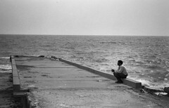 The man who can't be moved (nickvelarde) Tags: street seaside black white bw analog film nikonfilm nikonfm2 105ais ilfordfilm ilovefilm pindot filmdot filmdotlab kuwait pinoy mahabula d76developer