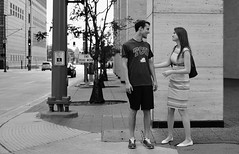 Early Love (burnt dirt) Tags: houston texas downtown city town mainstreet street sidewalk corner crosswalk streetphotography fujifilm xt1 bw blackandwhite girl man woman people person couple pair group crowd walking talking standing looking boots heels stilettos sandals model photographer camera lens dress skirt shorts glasses sunglasses purse bag phone cellphone pose longhair shorthair ponytail kneehigh blonde brunette headphones cap hat asian friends bike bicycle prom lovers