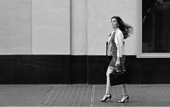 Another Successful Work Week (burnt dirt) Tags: texas downtown city town mainstreet street sidewalk corner crosswalk streetphotography xt1 fujifilm bw blackandwhite bag purse phone cellphone girl woman people person heels stilettos windy dress walking looking houston longhair