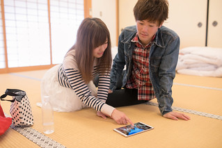 Young couple checking screen on digital tablet in Japanese tatami room