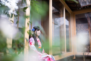Young woman in Kimono looking over Japanese garden from house