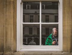 Framed chimper (phil anker) Tags: people street window frame chimping bath fujix70 photingo