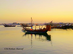 A Fishing Boat (M.RISHAN SHAREEF) Tags: nature native black beach boat culture red evening earth enjoy sea family thenature island lighting sky light morning man night ocean orange people qatar sun vehicle water work yellow