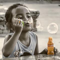 A timeless childhood experience (FotoGrazio) Tags: blowingbubbles filipina girl orange philippines play selectivecolor vigan waynegrazio waynesgrazio worldphotographer adorable bubblestuff bubbles childhood concentration cute fotograzio fun games kid littlegirl makingbubbles memories people pretty timeless vintage