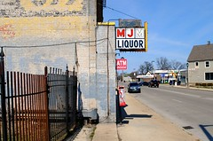 MJM Liquor, Milwaukee Wisconsin (Cragin Spring) Tags: midwest unitedstates usa unitedstatesofamerica mjmliquor sign liquor liquorstore liquors milwaukee city urban milwaukeewi milwaukeewisconsin wisconsin wi payphone street fence building