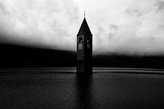 """Steeple in Lake Reschen"" (helmet13) Tags: d800e raw bw landscape lake thealps italy altoadige lakereschen reschensee steeple church clouds sky silence glockenturmderehemaligenpfarrkirchestkatharina artificiallake aoi heartaward peaceaward world100f platinumpeaceaward level3worldpeacehalloffame 200faves bestcapturesaoi"