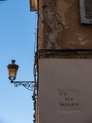 Rue Napoléon (ralfrings) Tags: beige blinds blue brown cable corsica cracked cracks decorative france glas house iron lamp lantern light mediterranian metal mounting paint plaster rusty scrolled sign sky sunny vintage wall weathered window