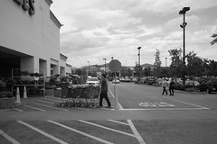 LowesCartPusher (ArielImages) Tags: leicam10 35mmsummilux leica bw lowes parkinglot streetphotography hardwarestore valencia